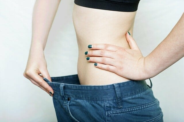 Uma mulher com umas calças demasiado grandes, perdendo peso