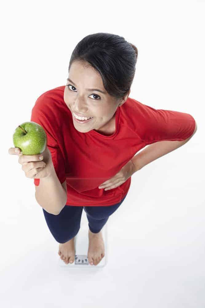 a mulher está segurando uma maçã em sua mão