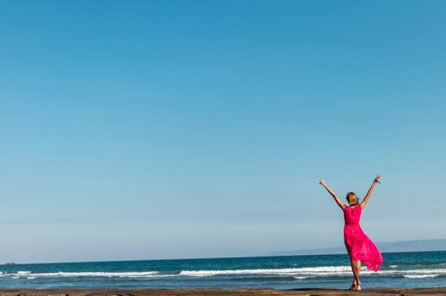 uma mulher com um vestido vermelho de pé na costa