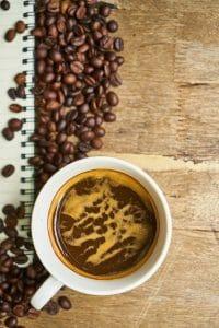 café em grão e café numa chávena