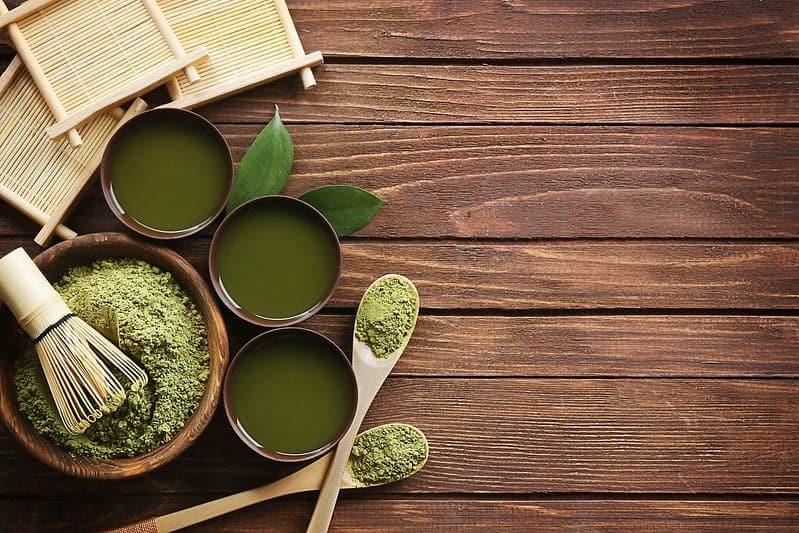 chá matcha verde em pó em salada e chávenas líquidas