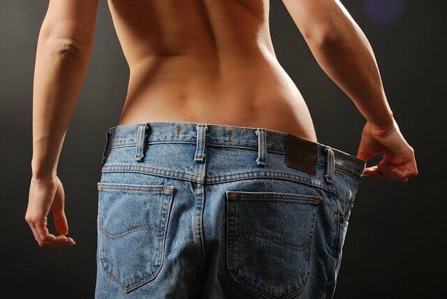 uma mulher magra com uma calça demasiado grande