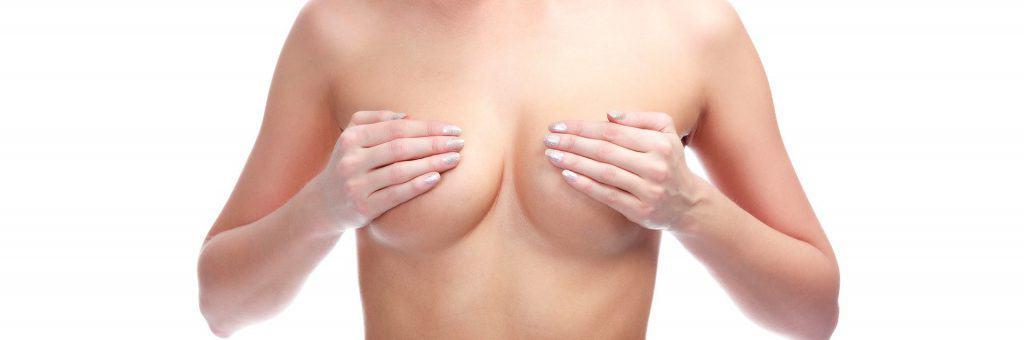 a mulher cobre os seus seios com as mãos