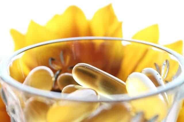 comprimidos num copo, flor amarela no fundo