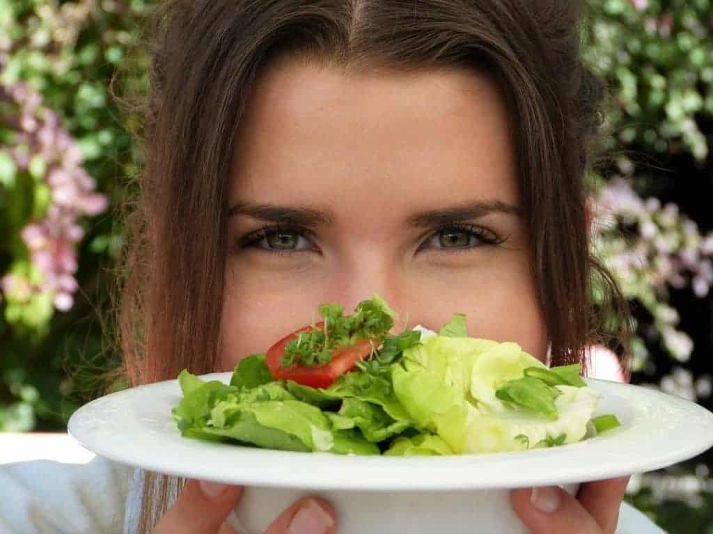 a mulher está a segurar um prato de salada