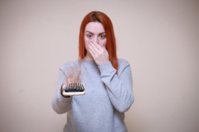 uma mulher olha para uma escova de cabelo cheia de cabelo