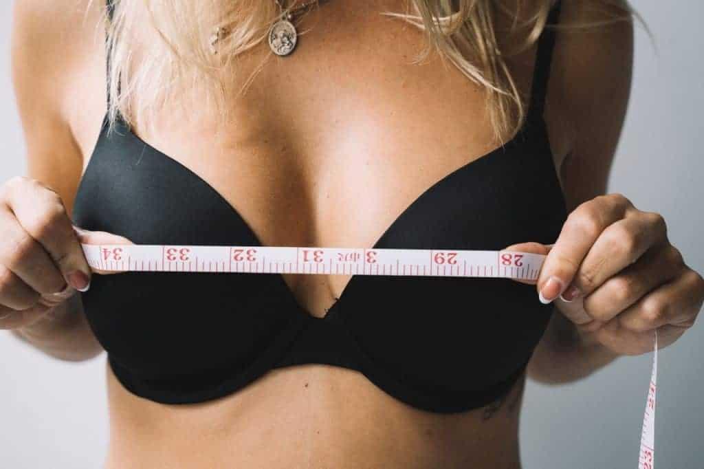 a mulher mede os seios com um centímetro
