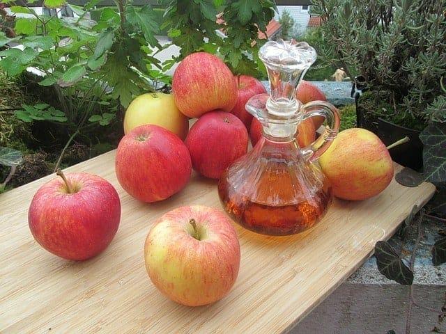 Maçã fresca e uma garrafa de vinagre de cidra de maçã em cima da mesa