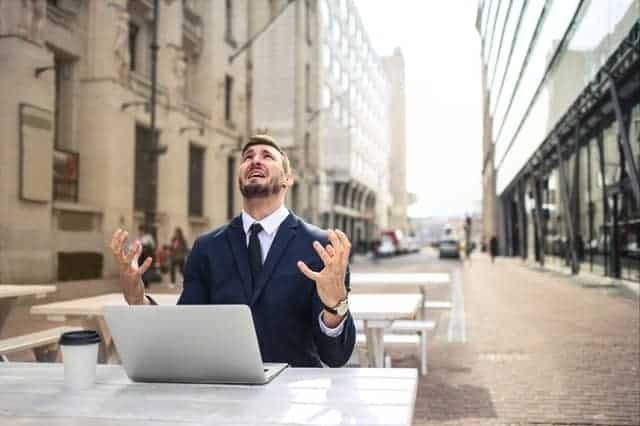 Um homem nervoso a trabalhar no seu portátil