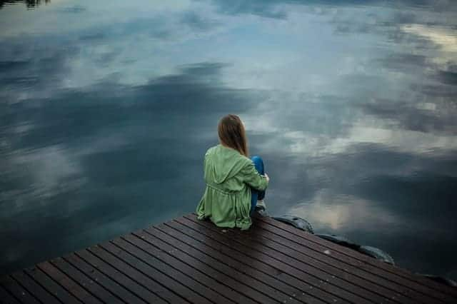 uma mulher senta-se à beira de um cais e olha para dentro de água