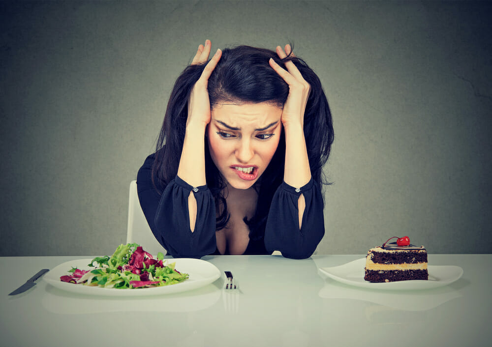 uma mulher senta-se à mesa com um prato de bolo e um prato de salada