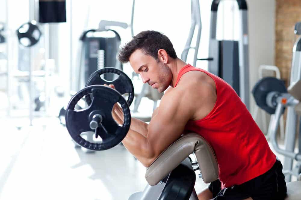 Um homem exercita-se com uma barra no ginásio.